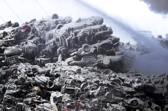 Ice-covered junk vehicles lie in a heap at the Northern Metal Recycling plant in Becker, Minn., on Wednesday morning, Feb. 19, 2020, as firefighters work at the site of a fire that had been burning for more than 24 hours. (David Joles/Star Tribune via AP)