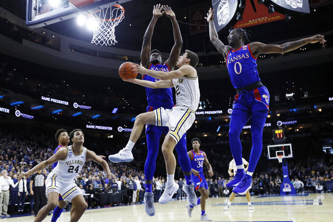 Villanova's Collin Gillespie, center, goes up for a shot between Kansas's Udoka Azubuike, left, and Marcus Garrett during the first half of an NCAA college basketball game, Saturday, Dec. 21, 2019, in Philadelphia. (AP Photo/Matt Slocum)