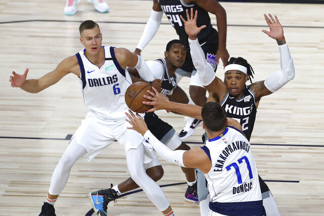 Dallas Mavericks guard Luka Doncic (77) passes the ball to forward Kristaps Porzingis (6) as Sacramento Kings center Richaun Holmes (22) defends during the first half of an NBA basketball game Tuesday, Aug. 4, 2020, in Lake Buena Vista, Fla. (Kim Klement/Pool Photo via AP)