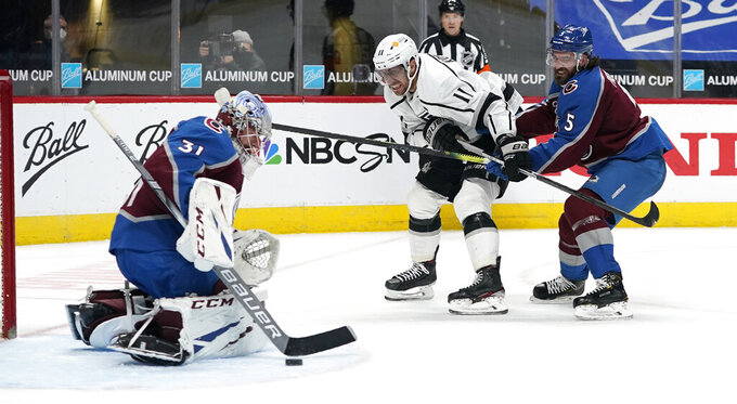 Los Angeles Kings center Anze Kopitar, center, drives past Colorado Avalanche defenseman Greg Pateryn to put a shot on goaltender Philipp Grubauer in the second period of an NHL hockey game Sunday, March 14, 2021, in Denver. (AP Photo/David Zalubowski)
