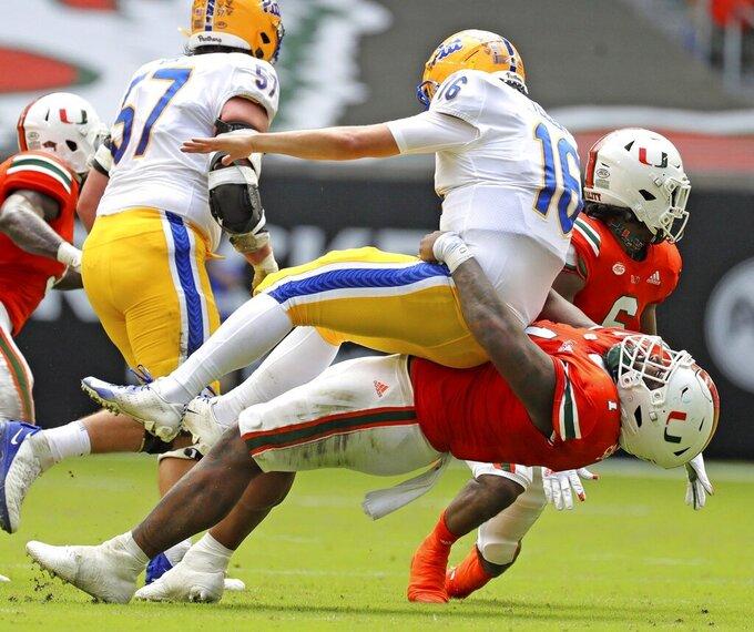 Miami defensive tackle Nesta Jade Silvera (1) tackles Pittsburgh quarterback Joey Yellen (16) in the second quarter of an NCAA college football game at Hard Rock Stadium in Miami Gardens, Fla., Saturday, Oct. 17, 2020. (Al Diaz/Miami Herald via AP)