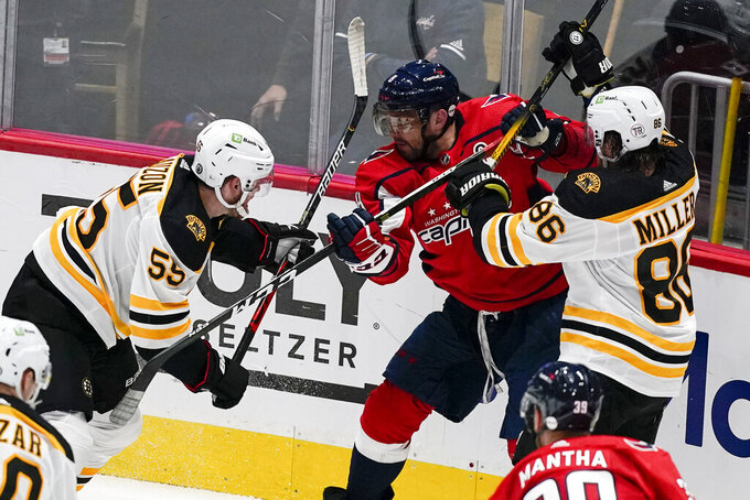 Boston Bruins defensemen Jeremy Lauzon (55) and Kevan Miller (86) combine to defend against Washington Capitals left wing Alex Ovechkin (8) during the second period of Game 1 of an NHL hockey Stanley Cup first-round playoff series Saturday, May 15, 2021, in Washington. (AP Photo/Alex Brandon)