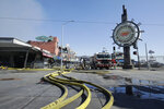 A runner passes over hoses after a fire broke out before dawn at Fisherman's Wharf in San Francisco, Saturday, May 23, 2020. A warehouse was destroyed. Fire officials said no injuries have been reported Saturday morning and firefighters are making multiple searches to ensure no one was inside the building on Pier 45. (AP Photo/Jeff Chiu)