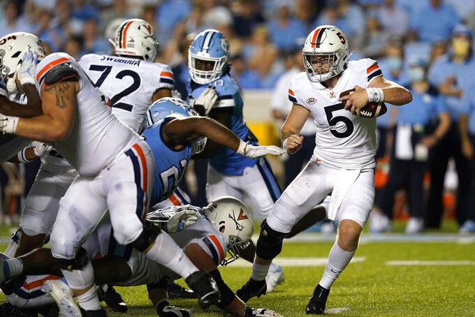 Virginia quarterback Brennan Armstrong (5) runs the ball against North Carolina during the first half of an NCAA college football game in Chapel Hill, N.C., Saturday, Sept. 18, 2021. (AP Photo/Gerry Broome)