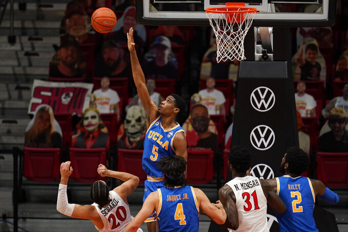 UCLA guard Chris Smith (5) blocks a shot from San Diego State guard Jordan Schakel (20) during the first half of an NCAA college basketball game Wednesday, Nov. 25, 2020, in San Diego. (AP Photo/Gregory Bull)
