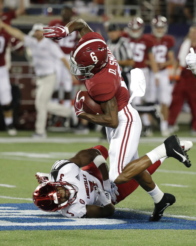 Alabama wide receiver DeVonta Smith (6) is stopped by Louisville cornerback Cornelius Sturghill after a reception during the first half of an NCAA college football game Saturday, Sept. 1, 2018, in Orlando, Fla. (AP Photo/John Raoux)