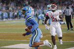 Tulane quarterback Justin McMillan (12) scores on a run, in  front of Houston linebacker Donavan Mutin (24) during the second half of an NCAA college football game in New Orleans, Thursday, Sept. 19, 2019. Tulane won 38-31. (AP Photo/Gerald Herbert)
