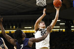 Iowa center Luka Garza, right, shoots over North Florida forward Wajid Aminu, left, during the first half of an NCAA college basketball game, Thursday, Nov. 21, 2019, in Iowa City, Iowa. (AP Photo/Charlie Neibergall)