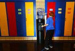 FILE- In this Sept. 4, 2018 file photo, a student gets water from a cooler in the hallway at Gardner Elementary School in Detroit. Some 50,000 Detroit public school students will started the school year by drinking water from coolers, not fountains, after the discovery of elevated levels of lead or copper. New Jersey's biggest city has recently been the epicenter of a problem with lead in drinking water, but the United States has an estimated 6 million lead pipes, many of them in unknown locations. (AP Photo/Paul Sancya, File)