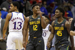 Baylor guard Jared Butler (12) smiles with teammate Davion Mitchell (45) while walking past Kansas guard Tristan Enaruna (13) following an NCAA college basketball game against Kansas in Lawrence, Kan., Saturday, Jan. 11, 2020. Baylor defeated Kansas 55-67. (AP Photo/Orlin Wagner)