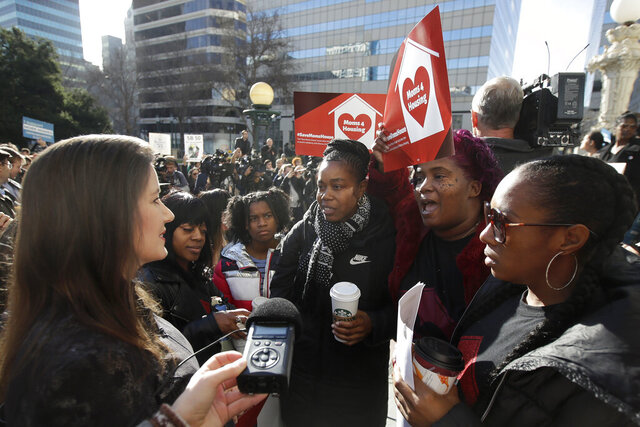 Oakland Mayor Libby Schaaf, left, talks with Misty Cross, second from left, Tolani King, center, Sharena Thomas, second from right, and Dominique Walker, all from the group Moms 4 Housing, at a rally outside of City Hall in Oakland, Calif., Tuesday, Jan. 7, 2020. Some California lawmakers said they support a group of homeless women who have been illegally living in a vacant three-bedroom house since November, partly to protest real estate speculators who drive up housing costs in the pricey San Francisco Bay Area. (AP Photo/Jeff Chiu)