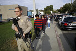 FILE - This Nov. 14, 2019 file photo shows a California Highway Patrol officer escorting students out of Saugus High School after a shooting on the campus in Santa Clarita, Calif. Authorities say the teenager who shot five classmates, killing two, at a Southern California high school used an unregistered