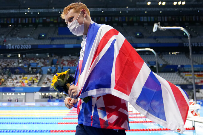 Tom Dean of Britain celebrates after winning the men's 200-meter freestyle at the 2020 Summer Olympics, Tuesday, July 27, 2021, in Tokyo, Japan. (AP Photo/Martin Meissner)