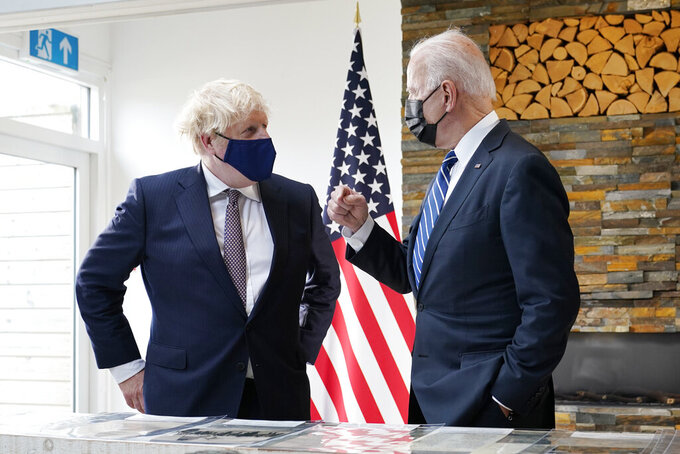 President Joe Biden and British Prime Minister Boris Johnson talk as they look over copies of the Atlantic Charter, during a bilateral meeting ahead of the G-7 summit, Thursday, June 10, 2021, in Carbis Bay, England.The Atlantic Charter is a copy of the original 1941 statement signed by FDR and Winston Churchill. (AP Photo/Patrick Semansky)