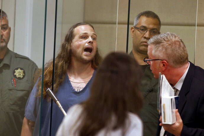 FILE - In this May 30, 2017, fie photo, Jeremy Christian shouts as he is arraigned in Multnomah County Circuit Court in Portland, Ore. Christian, charged with fatally stabbing two men who authorities say confronted him during a racist rant on a Portland, Oregon light-rail train, goes to trial Tuesday, Jan. 21, 2020, two years after the killings that plunged this liberal city into months of soul-searching. (Beth Nakamura/The Oregonian via AP, Pool, File)