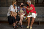 Women wearing face masks to prevent the spread of coronavirus talk as they sit in a square in Barcelona downtown, Spain, Wednesday Sept. 23, 2020. Spain is struggling to contain a second wave of the virus which has killed at least 30,000 people according to the country's health ministry. (AP Photo/Emilio Morenatti)