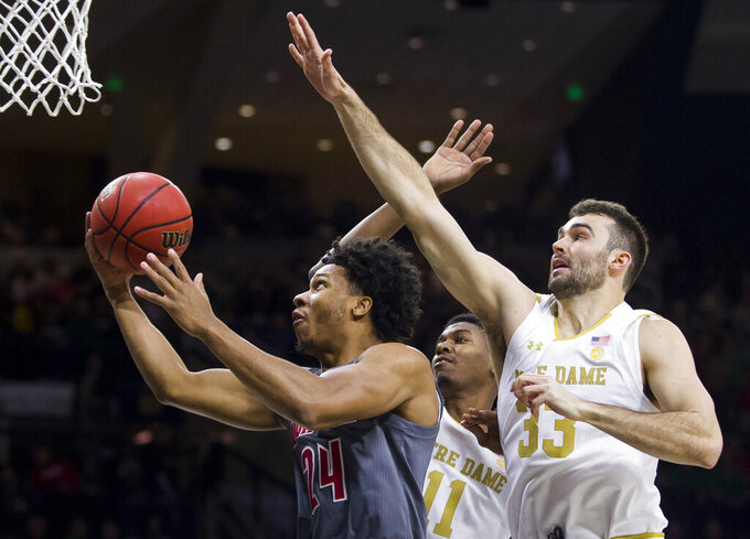 Louisville's Dwayne Sutton (24) goes up for a shot in front of Notre Dame's Juwan Durham (11) and John Mooney (33) during the first half of an NCAA college basketball game Saturday, Jan. 11, 2020, in South Bend, Ind. (AP Photo/Robert Franklin)
