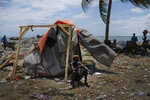 A woman sits outside her shelter in Cap-Haitien, Haiti, Thursday, July 22, 2021.  The city of Cap-Haitien will hold events to honor slain President Jovenel Moïse on Thursday ahead of Friday's funeral. (AP Photo/Matias Delacroix)
