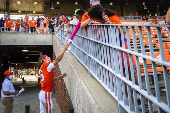Clemson quarterback Trevor Lawrence (16) hands a towel to Micah Chapman, 6, of Anderson, S.C., after an NCAA college football game against Syracuse in Clemson, S.C., on Saturday, Oct. 24, 2020. (Ken Ruinard/Pool Photo via AP)