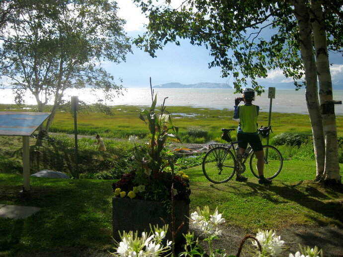 A cyclist takes in the St. Lawrence vista at Notre-Dame-du-Portage, Quebec, on Aug. 12, 2015. Along the south shore of the St. Lawrence River in this area of around Kamouraska, the panorama of river, sky, flowers and gardens defines the magic of bicycling the Route Verte network in Quebec. (AP Photo/Cal Woodward)