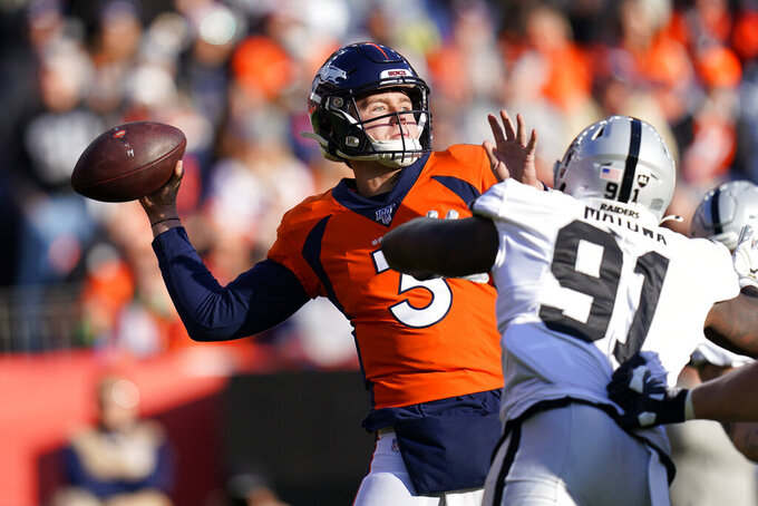 Denver Broncos quarterback Drew Lock throws a pass under pressure from Oakland Raiders defensive end Benson Mayowa (91) during the first half of an NFL football game Sunday, Dec. 29, 2019, in Denver. (AP Photo/Jack Dempsey)