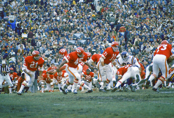 FILE - In this Jan. 11, 2970 file photo, Kansas City Chiefs quarterback Len Dawson prepares to handoff to running back Mike Garrett (21) as running back Robert Holmes (45) and guard Ed Budde (71) lead the play during the Super Bowl in New Orleans.   As the Chiefs prepare to play the San Francisco 49ers on Sunday, Feb. 2, 2020, many members of the 1970 team never lived to see the the Chiefs return to the championship game, and many others are in failing health.   (AP Photo, File)