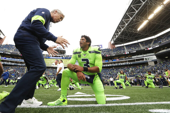 Seattle Seahawks coach Pete Carroll, left, talks with quarterback Russell Wilson during warmups for the team's NFL football game against the Los Angeles Rams, Thursday, Oct. 3, 2019, in Seattle. (AP Photo/Elaine Thompson)
