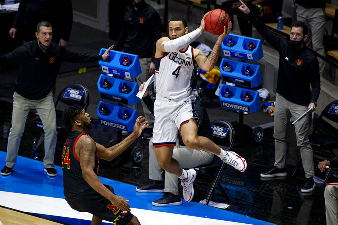 Connecticut's Tyrese Martin (4) saves the ball from going out of bounds, next to Maryland's Donta Scott (24) during the second half of a first-round game in the NCAA men's college basketball tournament Saturday, March 20, 2021, at Mackey Arena in West Lafayette, Ind. Maryland won 63-54. (AP Photo/Robert Franklin)