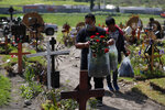 Men carry flowers as family members arrive to decorate the grave of a man who died of suspected COVID-19, in a section of the Municipal Cemetery of Valle de Chalco opened three months ago to accommodate the surge in deaths amid the ongoing new coronavirus pandemic, on the outskirts of Mexico City, Friday, Aug. 7, 2020. Mexico on Thursday jumped above 50,000 recorded deaths from COVID-19, the third-highest death toll in the world, behind only the United States and Brazil. (AP Photo/Rebecca Blackwell)