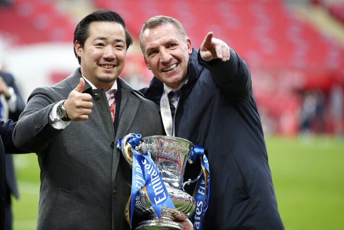 Leicester's manager Brendan Rodgers, right, and club chairman Khun Aiyawatt 'Top' Srivaddhanaprabha, left, hold the trophy after winning the FA Cup final soccer match between Chelsea and Leicester City at Wembley Stadium in London, England, Saturday, May 15, 2021. Leicester won 1-0. (Nick Potts/Pool via AP)