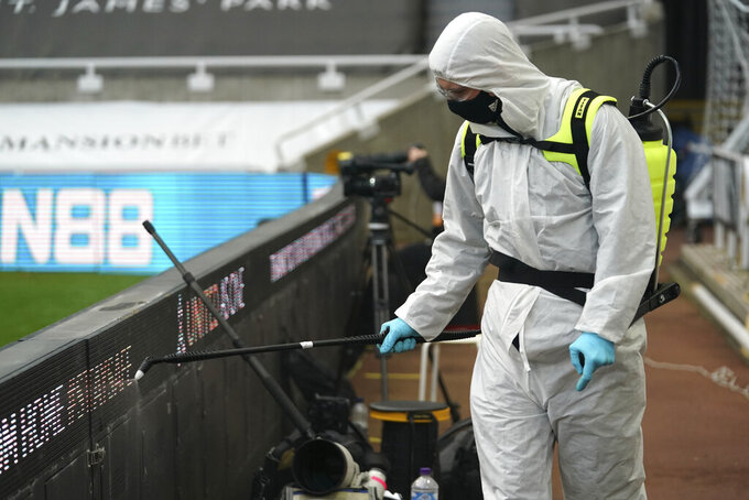 A worker disinfects part of the ground before an English Premier League soccer match between Newcastle United and Everton at the St. James' Park stadium in Newcastle, England, Sunday Nov. 1, 2020.(Owen Humphreys/Pool via AP)