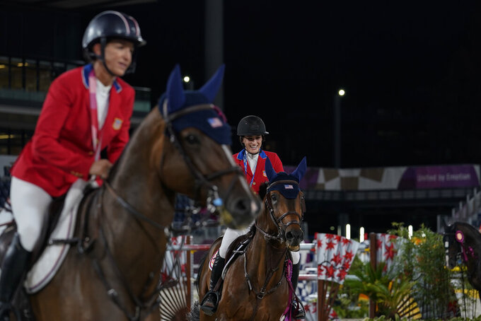 United States' Laura Kraut, riding Baloutinue, left, and United States' Jessica Springsteen, riding Don Juan van de Donkhoeve, take a victory lap around the stadium after winning a equestrian jumping team silver medal at the 2020 Summer Olympics, Saturday, Aug. 7, 2021, in Tokyo, Japan. (AP Photo/Carolyn Kaster)