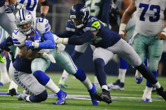 Dallas Cowboys running back Ezekiel Elliott (21) is hit by Seattle Seahawks linebacker Jake Martin (59) during the first half of the NFC wild-card NFL football game in Arlington, Texas, Saturday, Jan. 5, 2019. (AP Photo/Roger Steinman)