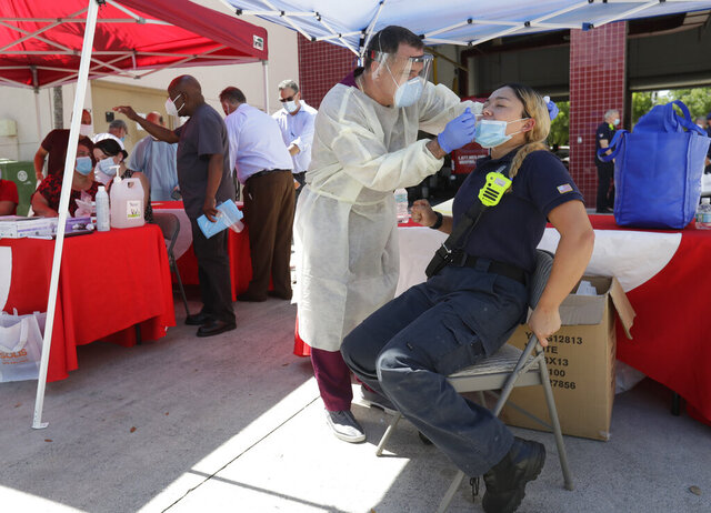 FILE - In this Aug. 6, 2020, file photo, Hialeah Fire Department Firefighter-Paramedic Laura Nemoga, right, winces as medical assistant Jesus Vera performs a COVID-19 test at Hialeah Fire Station #1, in Hialeah, Fla. The torrid coronavirus summer across the Sun Belt is easing after two disastrous months that brought more than 35,000 deaths. (AP Photo/Wilfredo Lee, File)