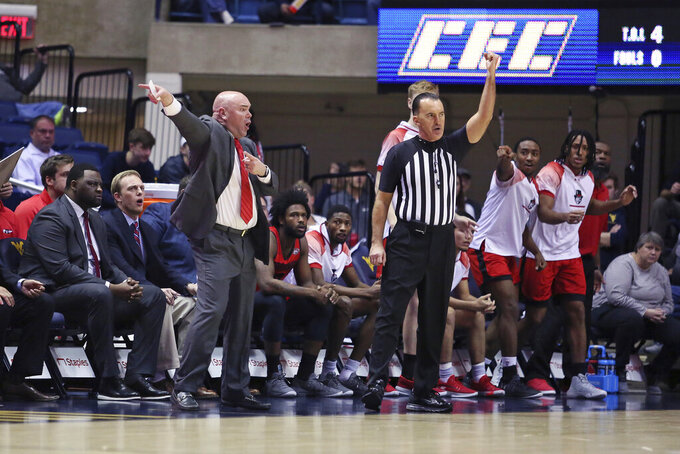 Austin Peay coach Matt Figger, front left, reacts during the first half of an NCAA college basketball game against West Virginia, Thursday, Dec. 12, 2019, in Morgantown, W.Va. (AP Photo/Kathleen Batten)