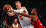 FILE - In this Nov. 22, 2017, file photo, Toronto Raptors forward Norman Powell (24) tries to strip the ball from New York Knicks forward Kristaps Porzingis (6) during the third quarter of an NBA basketball game in New York. The Knicks agree to trade injured star Kristaps Porzingis to Dallas Mavericks on Thursday, Jan. 31, 2019.  (AP Photo/Julie Jacobson, File)