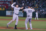 New York Yankees' Luke Voit, left, is congratulated by third base coach Phil Nevin (88) after hitting a home run against the Oakland Athletics during the fourth inning of a baseball game in Oakland, Calif., Friday, Aug. 27, 2021. (AP Photo/Jeff Chiu)