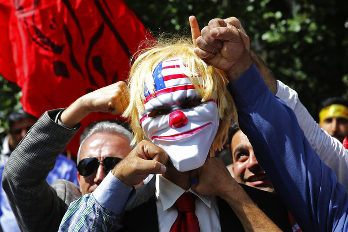 Iranian protesters pretend to punch a mask which mocks President Donald Trump in a show of anger over the deaths of nearly 60 Palestinians along the Gaza border on Monday, during a protest inside the former U.S. embassy in Tehran, Iran, Wednesday, May 16, 2018. State media reported that Iran's President Hassan Rouhani has condemned the killing of Palestinians by Israel, saying