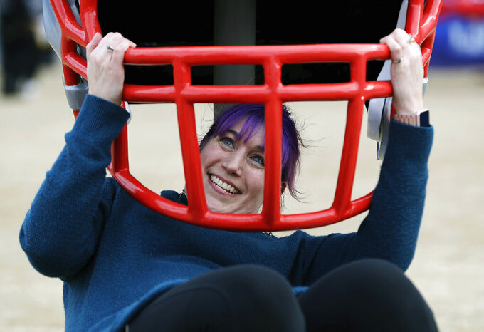 Amanda Smereage, of Boston, poses under a helmet before the NFL Super Bowl 53 football game between the Los Angeles Rams and the New England Patriots Sunday, Feb. 3, 2019, in Atlanta. (AP Photo/David J. Phillip)