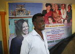 An Indian villager stands in front of a banner displaying photographs of U.S. Vice President-elect Kamala Harris in Thulasendrapuram, the hometown of Harris' maternal grandfather, south of Chennai, Tamil Nadu state, India, Tuesday, Jan. 19, 2021. The inauguration of President-elect Joe Biden and Vice President-elect Kamala Harris is scheduled be held Wednesday. (AP Photo/Aijaz Rahi)