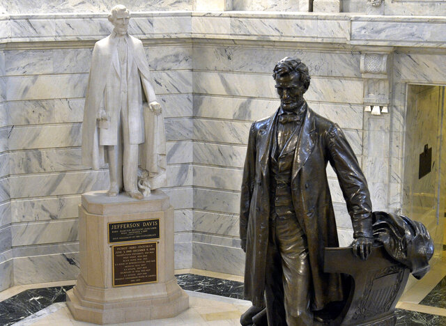 FILE - In this Aug. 5, 2015 file photo, a statue of Jefferson Davis, left, faces a statue of Abraham Lincoln in the Rotunda of the state Capitol in Frankfort, Ky. The statues tower over visitors to Kentucky's Capitol, but the state's governor doesn't think the Confederate president belongs in the same space as the U.S. president who helped end slavery. Democratic Gov. Andy Beshear said Thursday, June 4, 2020 that he sees the Davis statue as a divisive symbol that should be removed from the Capitol Rotunda. (AP Photo/Timothy D. Easley, File)