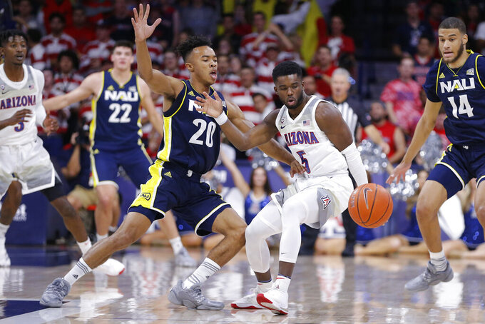 Northern Arizona guard Cameron Shelton (20) and Arizona guard Max Hazzard (5) watch the ball during the first half of an NCAA college basketball game Wednesday, Nov. 6, 2019, in Tucson, Ariz. (AP Photo/Rick Scuteri)