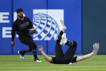 Chicago White Sox center fielder Adam Engel, right, rolls over after catching a ball hit by Texas Rangers' Scott Heineman (not shown) as teammate Leury Garcia, left, watches during the fifth inning of a baseball game Saturday, Aug. 24, 2019, in Chicago. (AP Photo/Jeff Haynes)
