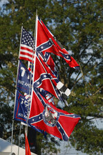 A vendor displays Confederate Battle flags as well as Trump 2020 flags across from the Speedway during the NASCAR Xfinity auto race at the Talladega Superspeedway in Talladega Ala., Saturday June 20, 2020 (AP Photo/John Bazemore)