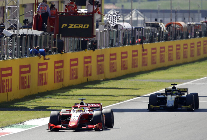 Prema driver Mick Schumacher of Germany, left, crosses the finish line to take fourth place during the F2 Sprint Race ahead of the Grand Prix of Tuscany, at the Mugello circuit in Scarperia, Italy, Sunday, Sept. 13, 2020. (AP Photo/Luca Bruno)