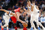 Dallas Mavericks guard Seth Curry, left, Kristaps Porzingis, right, and Toronto Raptors center Marc Gasol, center, chase after the ball in the second half of an NBA basketball game in Dallas, Saturday, Nov. 16, 2019. (AP Photo/Tony Gutierrez)