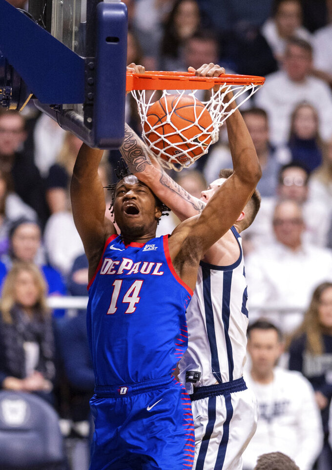 DePaul center Nick Ongenda (14) scores with a slam dunk while Butler forward Sean McDermott, right,makes contact with his head during the second half of an NCAA college basketball game, Saturday, Feb. 29, 2020, in Indianapolis. (AP Photo/Doug McSchooler)