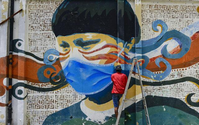 A street artist spray paints a protective face mask over an old mural featuring a Venezuelan Indigenous man, in Caracas, Venezuela, Saturday, July 18, 2020, amid the new coronavirus pandemic. (AP Photo/Matias Delacroix)