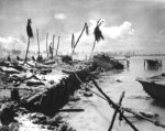 FILE - In this November 1943 file photo, bodies and wrecked amphibious tractors litter a battlefield, after U.S. Marines from the 2nd Division forced back the Japanese on Betio island in the Tarawa Atoll, Kiribati. A nonprofit organization that searches for the remains of U.S. servicemen lost in past conflicts has found what officials believe are the graves of more than 30 Marines and sailors killed in one of the bloodiest battles of World War II. (AP Photo, File)
