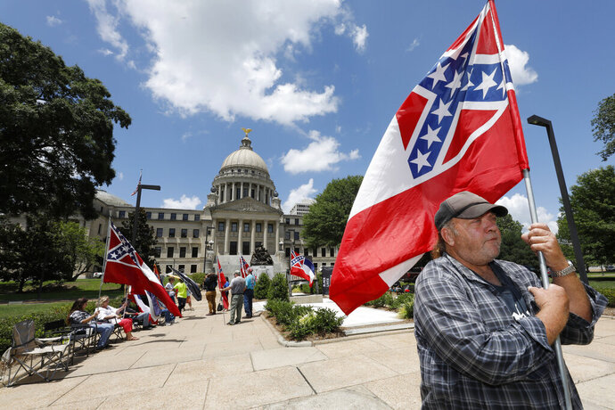 FILE - In this Sunday, June 28, 2020, file photo, David Flynt of Hattiesburg, stands outside the state Capitol with other current Mississippi flag supporters in Jackson, Miss.